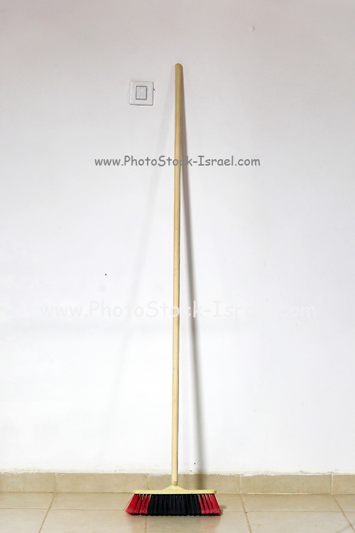Broom leans against a wall