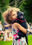 A young girl holding a small black dog