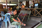 Native men in pool room café on the side of the road. Home of the Kenyah native people who once lived in Long Geng, which was flooded by the Bakun Dam. Their community is now dispersed between Sungai Asap, Long Lewan and floating longhouses on the Bakun reservoir. Bakun Belaga region, Sarawak Borneo 2012..Borneo native peoples and their rainforest habitat revisited two decades later: 1989/1991-2012. ..The Bakun hydro-electric dam, which covers 700km². Construction of the dam required the relocation of more than 9,000 native residents, mainly Kayan and Kenyah indigenous peoples who lived in the flooded area. Many Sarawak natives have been relocated to a longhouse settlement named Sungai Asap in Bakun. Most of them were subsistence farmers. Each family were promised only 3 acres of land, insufficient to survive, and many families still have not been compensated for the loss of their longhouses..Sarawak's primary rainforests have been systematically logged over decades, threatening the sustainable lifestyle of its indigenous peoples who relied on nomadic hunter-gathering and rotational slash & burn cultivation of small areas of forest to survive. Now only a few areas of pristine rainforest remain; for the Dayaks and Penan this spells disaster, a rapidly disappearing way of life, forced re-settlement, many becoming wage-slaves. Large and medium size tree trunks have been sawn down and dragged out by bulldozers, leaving destruction in their midst, and for the most part a primary rainforest ecosystem beyond repair. Nowadays palm oil plantations and hydro-electric dam projects cover hundreds of thousands of hectares of what was the world's oldest rainforest ecosystem which had some of the highest rates of flora and fauna endemism, species found there and nowhere else on Earth, and this deforestation has done irreparable ecological damage to that region.