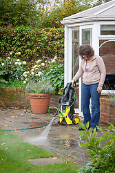 Pressure washing a patio with a jet spray in autumn