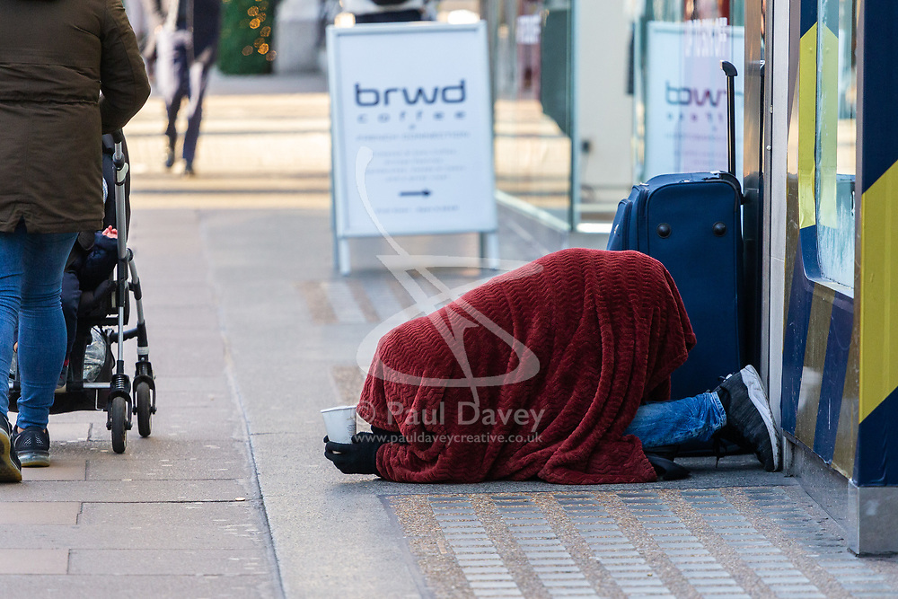 A man covered in a blanket against the morning chill begs on Oxford Street in London as Eastern European beggars and street performers take advantage of the UK's relative wealth, squeezing opportunities for the UK's own homeless. London, December 13 2018.