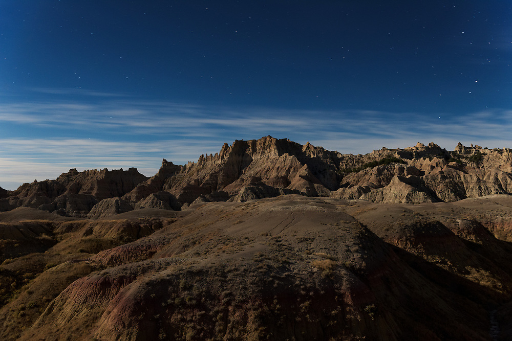 Light from a full moon illuminates the surrounding landscape that makes up the northern area of Badlands National Park.