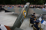 Royal Air Force (RAF) musicians play near full-size Spitfire replica at the 70th anniversary of WW2 Battle of Britain. This iconic fighter plane helped stop a full-scale Nazi invasion of the British Isles and crowds gathered along Horseguards in central London to hear the actor Robert Hardy deliver Winston Churchill's famous speech when he praised the young RAF pilots fend off the Nazi Luftwaffe, ahead of a full-scale invasion of the British Isles. The musicians consisting of Saxophone players entertain the people in the background before a fly-past above.