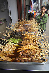 Boy looking at  selection of snack food on street outside small restaurant in Beijing China