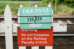 Sign of The Samaritans attached to railway level crossing in the UK.