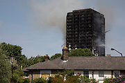 Emergency fire services tackle a blaze at Grenfell Tower near Notting Hill on 14th June 2017 in West London, United Kingdom. The huge fire engulfed the tower block, trapping many people in their homes. A number of fatalities are reported. The block of flats in the Borough of Kensington and Chelsea,billowed large plumes of smoke way above the capital after the blaze broke out in the early hours of Wednesday morning. Londoners came out on the streets to help, offer food and water, support and assistance to those who had lost their homes or didn't know the whereabouts of their friends and family.