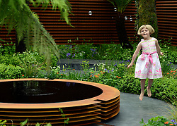 © Licensed to London News Pictures. 21/05/2012. Chelsea, UK. Martha Flemons aged 5 jumps in the air as she plays with bubbles in 'The World Vision Garden' her father Sim Flemons is one of the designers for the garden.  Press preview of The Chelsea Flower Show today 21 May 2012. The world's most famous flower show, which has been held in the grounds of the Royal Chelsea Hospital since 1913, will be open to the public from Tuesday. Visitors are expected to flock in their thousands to see displays of plants, flowers and furniture for ideas on how to decorate their gardens.. Photo credit : Stephen Simpson/LNP