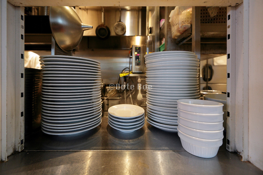 restaurant kitchen window with stack of plates