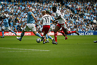 Photo: Peter Phillips.<br /> Manchester City v Olympiacos. Pre Season Friendly.<br /> 06/08/2005.<br /> Predrag Djordjevic squeezes a  shot in despite the attention of Citys Danny Mills