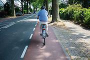 Een man rijdt met een helm op een elektrische fiets door Huizen.<br /> <br /> A man on an electric bike rides in Huizen.