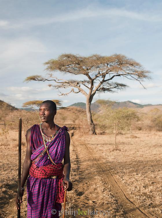 Young Maasai tribesman walking down a dirt road in Chyulu Hills National Park