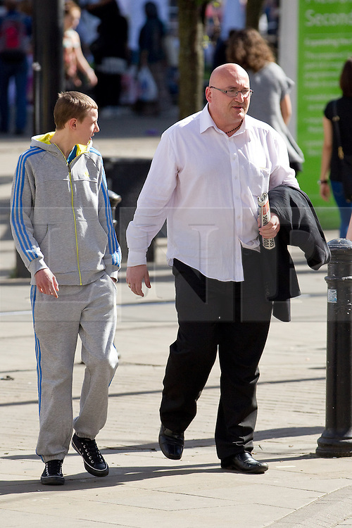 © Licensed to London News Pictures .  08/09/2012 . Manchester, UK . Domenyk Noonan (right) , recently released from prison , walks through Manchester 's Piccadilly Gardens , accompanied by his Nephew , Kieran Noonan (left) . The area was the scene of looting and rioting on 9th August 2011 , during which Noonan was arrested . Noonan has announced he plans to sue the police over the  arrest . Under the terms of a previous early release , the arrest lead to him being recalled to prison . Photo credit : Joel Goodman/LNP