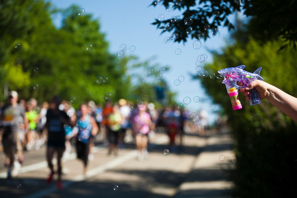 A bystander playfully shoots bubbles at competitors running the 2012 Bolder Boulder 10K road race in Boulder, Colorado.