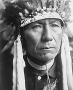 Head-and-shoulders portrait of a Nez Percé man in full feather headdress, 1910. Photograph by Edward Curtis (1868-1952).