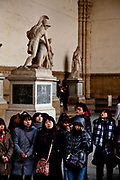 Tourists visiting Romano Greek statues in the Loggia dei Lanzi, Florence.<br /> Piazza della Signoria is an L-shaped square in front of the Palazzo Vecchio in Florence, Italy. It was named after the Palazzo della Signoria, also called Palazzo Vecchio.<br /> It is the focal point of the origin and of the history of the Florentine Republic and still maintains its reputation as the political hub of the city.It is the meeting place of Florentines as well as the numerous tourists, located near Ponte Vecchio and Piazza del Duomo and gateway to Uffizi Gallery.<br /> The Loggia dei Lanzi consists of wide arches open to the street, three bays wide and one bay deep. The arches rest on clustered pilasters with Corinthian capitals. The wide arches appealed so much to the Florentines, that Michelangelo even proposed that they should be continued all around the Piazza della Signoria<br /> It is effectively an open-air sculpture gallery of antique and Renaissance art including the Medici lions.