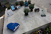 "Decorated grave for singer and actor Gilbert Becaud, in the Pere Lachaise cemetery, Paris. Gilbert Bécaud (1927 - 2001 was a French singer, composer and actor, known as ""Monsieur 100.000 Volts"" for his energetic performances. His best-known hits are ""Nathalie"" and ""Et Maintenant"", a 1961 release that became an English language hit as ""What Now My Love"". He remained a popular artist for nearly fifty years, identifiable in his dark blue suits, with a white shirt and ""lucky tie""; blue with white polka dots."