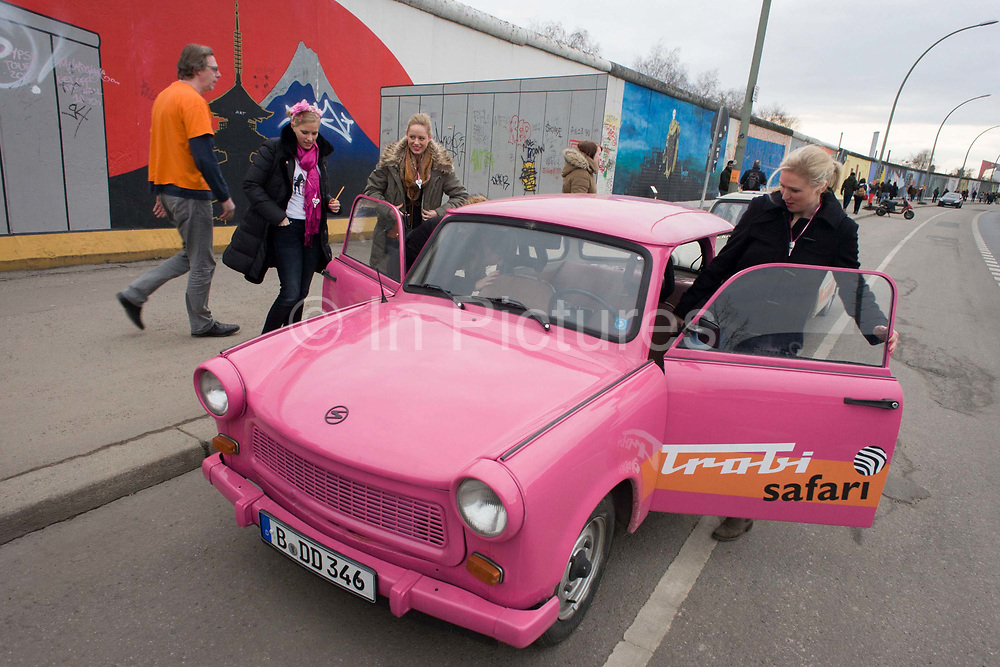 """Visitors enjoy the art and an old Trabant car at the old Berlin Wall at the East Side Gallery, the former border between Communist East and West Berlin during the Cold War. Trabants were the common Socialist vehicle in East Germany, exported to countries both inside and outside the communist bloc. The Berlin Wall was a barrier constructed by the German Democratic Republic (GDR, East Germany) that completely cut off (by land) West Berlin from surrounding East Germany and from East Berlin. The Eastern Bloc claimed that the wall was erected to protect its population from fascist elements conspiring to prevent the """"will of the people"""" in building a socialist state in East Germany. In practice, the Wall served to prevent the massive emigration and defection that marked Germany and the communist Eastern Bloc during the post-World War II period."""