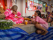 "05 APRIL 2015 - CHIANG MAI, CHIANG MAI, THAILAND: A Tai Yai boy being ordained as a Buddhist novice jokes with his sister after lunch during the second day of the three day long Poi Song Long Festival in Chiang Mai. The Poi Sang Long Festival (also called Poy Sang Long) is an ordination ceremony for Tai (also and commonly called Shan, though they prefer Tai) boys in the Shan State of Myanmar (Burma) and in Shan communities in western Thailand. Most Tai boys go into the monastery as novice monks at some point between the ages of seven and fourteen. This year seven boys were ordained at the Poi Sang Long ceremony at Wat Pa Pao in Chiang Mai. Poy Song Long is Tai (Shan) for ""Festival of the Jewel (or Crystal) Sons.    PHOTO BY JACK KURTZ"