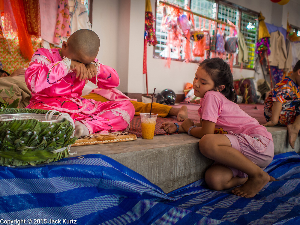 """05 APRIL 2015 - CHIANG MAI, CHIANG MAI, THAILAND: A Tai Yai boy being ordained as a Buddhist novice jokes with his sister after lunch during the second day of the three day long Poi Song Long Festival in Chiang Mai. The Poi Sang Long Festival (also called Poy Sang Long) is an ordination ceremony for Tai (also and commonly called Shan, though they prefer Tai) boys in the Shan State of Myanmar (Burma) and in Shan communities in western Thailand. Most Tai boys go into the monastery as novice monks at some point between the ages of seven and fourteen. This year seven boys were ordained at the Poi Sang Long ceremony at Wat Pa Pao in Chiang Mai. Poy Song Long is Tai (Shan) for """"Festival of the Jewel (or Crystal) Sons.    PHOTO BY JACK KURTZ"""