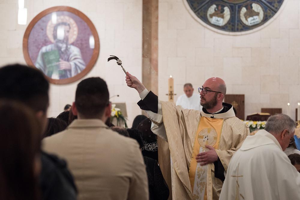 20 April 2019, Jerusalem: Father Bernard sprinkles water over the congregants during Holy Saturday service at Saint James' Church in Beit Hanina, Jerusalem.