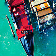 An empty gondola docked at a worn out pier in the city of Venice, Italy.<br /> <br /> LICENSING: This image can only be licensed through SpacesImages. Click on the link below:<br /> <br /> http://tinyurl.com/cug6dnd