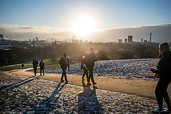 © Licensed to London News Pictures. 10/02/2021. London, UK. Members of the public take an early morning walk as he sun rises over the city of London, as seen from Primrose Hill in Camden, north London, on another morning of sub zero temperatures in the capital. Photo credit: Ben Cawthra/LNP