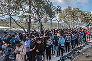 Lesbos, Greece, 06/03/20   A large group of male migrants are praying in front of the fences of the Moria refugee camp on Lesbos.
