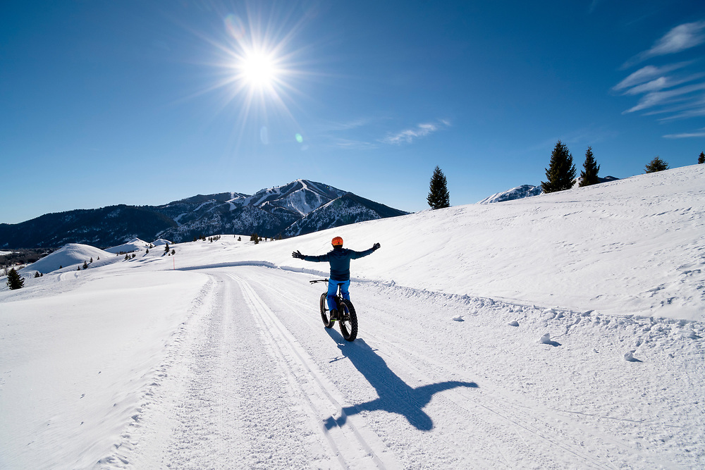No Hands Snow Biking the Diamond Back Nordic Trail on the White Clouds Golf Course at Sun Valley Resort in Idaho with Baldy Mountain in background.  Licensing and Open Edition Prints.