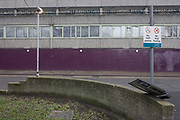 Urban landscape of a curved wall, street signs and security fencing on the Aylesbury Estate, on 4th January, London borough of Southwark, England.