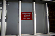 """""""No prisoners allowed beyond this point"""" red warning sign on a grey security door guarded by a metal door gate in HMP Pentonville, London, UK.  HM Prison Pentonville is an English Category B men's prison, operated by Her Majesty's Prison Service. Pentonville Prison is located on  Caledonian Road in the Barnsbury area of the London Borough of Islington, north London, United Kingdom. (Photo by Andy Aitchison)"""