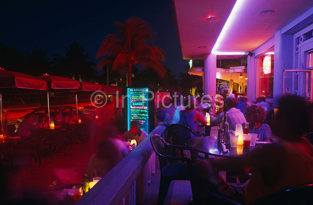 Crowds of visitors and locals gather on the terrace of an Ocean Drive cafe in Miami Beach. It is early evening and we see the blurred people moving about over the picture during a time-exposure of a few seconds. The colours of ambient neon lights that these streets are well-known for have become very vivid with bright pinks and reds a main feature of this scene. A menu board listing cocktail drinks prices stands on the sidewalk. Candles have been lit in glass jars on table tops. Ghostly, blurred Palm trees sway about in the coastal breeze against the fading sky of early evening. This is a vibrant district of tropical Miami, Florida. The place to hang-out and be noticed. Glowing pinks and blues are vivid in this scene where beautiful people and expensive cars cruise along slowly, each parading bodywork and personality.