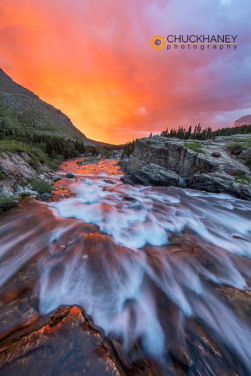 Brlliant sunrise sky over Swiftcurrent Falls in Glacier National Park, Montana, USA