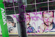 Seen through the purple swirls of graffiti marking the window of a bus driving through south London, the faces outside a branch of an ASDA supermarket on the Old Kent Road, on 21st March 2019, in London, England.
