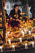 A elderly woman lights candles around the gravesite of a family member during the Day of the Dead festival October 31, 2017 in Tzintzuntzan, Michoacan, Mexico.
