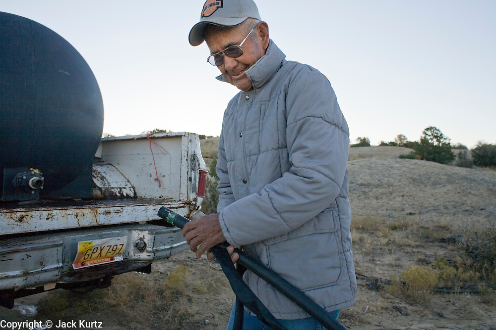 22 OCTOBER 2007 -- COYOTE CANYON, NM: MARK TSOSIE, 78 years old, a member of the Navajo Nation, releases water from his pickup truck into his home made irrigation system in Peach Springs Wash near Coyote Canyon. Tsosie has been hauling water all his life. He started working for the railroad when he was 14 years old. His job was to haul water to the workers. Now retired and he's still hauling water except now he hauls it to his home. More than 30 percent of the homes on the Navajo Nation, about the size of West Virginia and the largest Indian reservation in the US, don't have indoor plumbing or a regular supply of domestic water. Many of these homes have to either buy water from commercial vendors or haul water from public wells. A Federal study showed that the total cost of hauling water was about $113 per 1,000 gallons. A Phoenix household, in comparison, pays just $5 a month for up to 7,400 gallons of water. The lack of water on the reservation means the Navajo are among the most miserly users of water in the United States. Families that have to buy or haul water use only about 15 gallons of water per day per person. In Phoenix, by comparison, the average water use is about 170 gallons per day.  Photo by Jack Kurtz