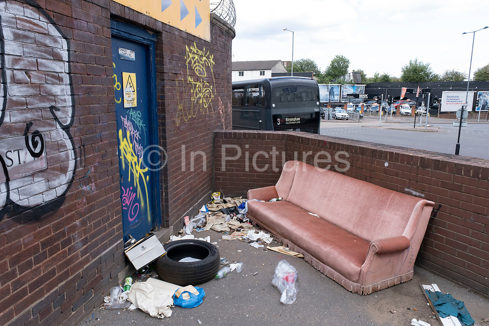Old sofa dumped at a main road junction in Bordesley on 3rd August 2020 in Birmingham, United Kingdom.  Illegal dumping, also called fly dumping or fly tipping, is the dumping of waste illegally instead of using an authorised method such as kerbside collection or using an authorised rubbish dump. It is the illegal deposit of any waste onto land, including waste dumped or tipped on a site with no licence to accept waste.