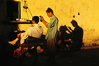 """Street barber on a corner in Saigon, Vietnam, ca. 1995<br /> Available as Fine Art Print in the following sizes:<br /> 08""""x12""""US$   100.00<br /> 10""""x15""""US$ 150.00<br /> 12""""x18""""US$ 200.00<br /> 16""""x24""""US$ 300.00<br /> 20""""x30""""US$ 500.00"""
