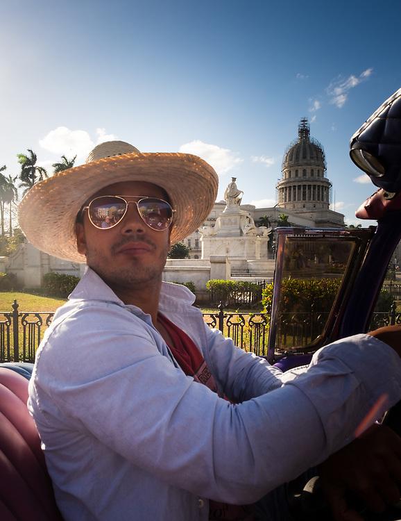 HAVANA, CUBA - CIRCA MAY 2016: Taxi driver of old convertible classic car driving through the Capitol in Havana