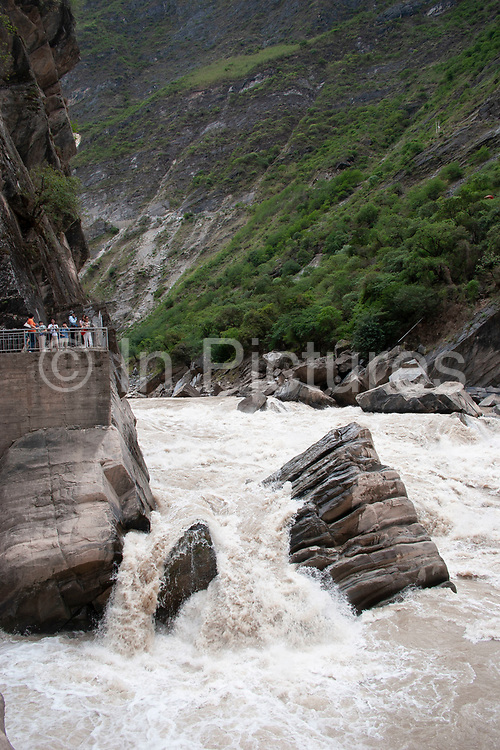 Tiger Leaping Gorge or Hu Tiao Xiao, in amongst the foothills of the Himalayan mountains near Daju, Yunnan, China. The Jinsha Jiang river cuts through the soft rocks creating dramatic steep gorges. At one point in the centre of the river a hard piece of granite which eroded at a much slower pace to the surrounding rock, rises out of the river pushing the fast flowing water up in a dramatic white water rapids. Tiger Leaping Gorge is a popular tourist destination where many Chinese travel to see the landscape named after their most honoured animal.