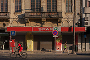 Two young men, one a cyclist and the other in a sports vest, pass each other on the street, outside the premises of a Spar supermarket, on 17th July, at Avenida Dr. Lourenco Peixnho, in Aveiro, Portugal.