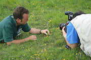 Ranger poses with orchid for the press at opening of new National Nature Reserve. Durlston, Dorset, UK.