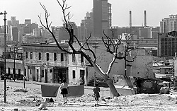 """District 6 demolition.jpg<br /> Two girls cross a barren wasteland facing one of the few surviving rows of tenements in flattened District Six. The last few families left the area in June 1982. Dr Oscar Wollheim referred at the time to the re-proclamation of District Six for white occupation as """"an act of piracy for which I can find no parallel in the modern civilised world"""".<br /> Picture: Jim McLagan"""