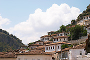 The modern lower part of the village crawling up the hillside with white washed ottoman style houses. Berat lower town. Albania, Balkan, Europe.