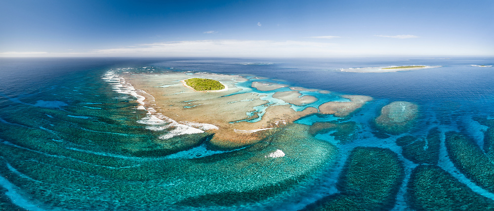 This is an aerial panorama of Maninita Island in the Vava'u island group of the Kingdom of Tonga. The island sits atop an extensive coral reef structure, which is for the most part not visible from the surface of the ocean. Visible to the right behind Maninita is Taula Island.