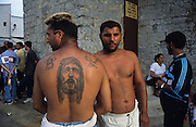 Gitan with a tattoo of Jesus Christ. Place de l'Eglise, Saintes Maries de la Mer<br /><br />Europe, France, Camargue, Saintes Maries de la Mer. The seaside town in the Camargue hosts a Gypsy festival once a year during May, where its landscape undergoes great changes. Otherwise it is a land bordered by sea, lakes and ponds, populated by flamengos, bulls and horses.