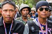 17 FEBRUARY 2014 - BANGKOK, THAILAND: Security guards from the anti-government protestors march into the Ministry of Education offices on Ratchadamnoen Avenue. The anti-government protest movement, led by the People's Democratic Reform Committee and called Shutdown Bangkok has been going on for more than a month. The protest movement called, the People's Democratic Reform Committee (PDRC), wants to purge the current ruling party and its patrons in the Shinawatra family from Thai politics. The movement has consistently refused any dialogue or negotiations with the Pheu Thai ruling party. Over the weekend Thai police claimed to have taken the protest areas around Government House (the Prime Minister's office) away from protestors but on Monday protestors marched unimpeded to Government House and retook the area.   PHOTO BY JACK KURTZ