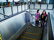 06 DECEMBER 2018 - SAMUT PRAKAN, THAILAND:  Women ride the escalator up to the platform of the Kheha station, the last station on the BTS Skytrain east extension. The 12.6 kilometer (7.8 miles) east extension of the Sukhumvit Line of the Bangkok BTS Skytrain goes into Samut Prakan, a town east of Bangkok.  The system is now 51 kilometers long (32 miles), including the 12.6 kilometer extension that opened December 06. About 900,000 people per day use the BTS.     PHOTO BY JACK KURTZ