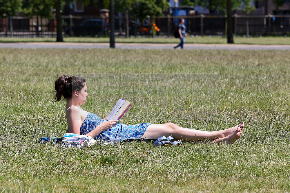© Licensed to London News Pictures. 22/06/2020. London, UK. A woman reads a book in Finsbury Park, north London on a warm and sunny day in the capital. According to the Met Office, the temperatures are forecast to reach between 31 and 33 degrees celsius in the south-east of England later this week. Photo credit: Dinendra Haria/LNP