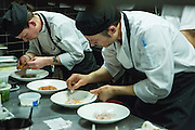 Chefs plating in the kitchen of Pearl & Ash.