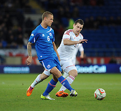 Sam Vokes of Wales (Burnley) chases down Ragnar Sigurdsson (FK Kransnodar) of Iceland - Photo mandatory by-line: Dougie Allward/JMP - Tel: Mobile: 07966 386802 03/03/2014 -